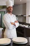 Happy head chef standing with arms crossed behind counter. In a commercial kitchen royalty free stock photo