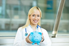 Happy health care professional, doctor, nurse holding piggy bank Stock Photography