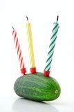 Happy Healthy Birthday!. Birthday humor: green cucumber with birthday candles instead of a cake. Associates with diet and healthy food. White background Stock Photography