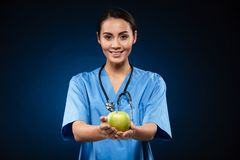 Happy healthy doctor holding green apple isolated