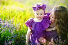 Happy healthy family concept. A young beautiful woman with her little cute daughter walking in the wheat gold field on a royalty free stock photos