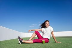 Happy healthy green smoothie fitness athlete woman. Healthy fitness Asian woman drinking green smoothie. Happy relaxing sporty athlete during strength training royalty free stock image