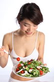Happy healthy Japanese girl eating green salad. Beautiful, smiling young Japanese girl, wearing white sports bra, showing off a healthy body while eating a green royalty free stock images