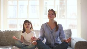 Happy healthy kid daughter and mother having fun doing yoga