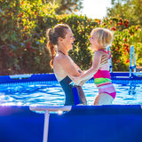Happy healthy mother and child in swimming pool playing Stock Images