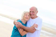 Happy healthy retired elders couple enjoying vacation on the beach royalty free stock photo