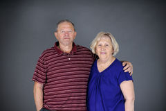 Happy and healthy senior couple. Looking at camera, studio shot over grey background Stock Image