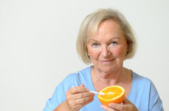 Happy healthy senior lady with a orange Royalty Free Stock Image