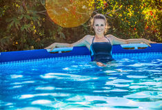 Happy healthy woman in blue swimwear in swimming pool relaxing Royalty Free Stock Photos