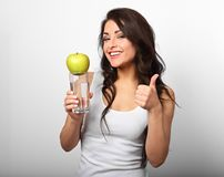Happy healthy woman holding apple and clear water in hand, showi Stock Photography
