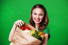 Happy healthy woman with a paper bag of vegetables. on green background. Stock Photos