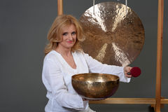 Happy healthy woman playing the singing bowl. Stock Photography