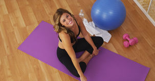 Happy healthy young woman smiling on workout mat Royalty Free Stock Photo