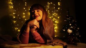 Cheerful girl having fun on new year eve. Happy hearty lady smiling, enjoying and raving in illuminated twinkling room. Taking pleasure and relaxing young Royalty Free Stock Images