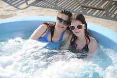 Happy Heating Up. A mom and preteen daugher enjoying a dip in an outdoor hot tub on a sunny day Stock Image