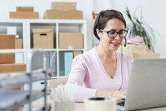 Happy helpdesk operator consulting clients online. Happy helpdesk operator speaking in microphone of headset while consulting clients online stock image