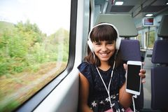 She is happy with her smart phone travelling by train royalty free stock images