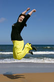 Happy high jump. A beautiful red hair white young woman with happy smiling facial expression jumping and raising up her arms in the blue clear sky royalty free stock images