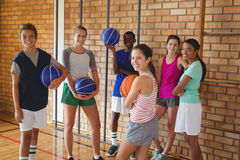 Happy high school kids standing with basketball in the court stock images