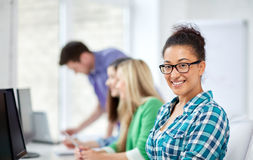 Happy high school students in computer class. Education, people, friendship, technology and learning concept - group of happy international high school students Royalty Free Stock Image