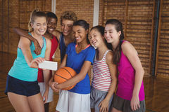 Happy high school team taking a selfie with mobile phone. In the court Royalty Free Stock Photos