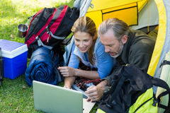 Happy hiker couple using laptop. In tent Stock Image