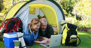 Happy hiker couple using laptop. In tent, 4k stock footage