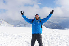 Happy hiker enjoy life and beautiful landscape in winter mountai. Ns. On the background snow-covered mountains and blue sky Royalty Free Stock Image