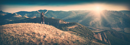 Happy hiker. Instagram filter stylisation. Hiker with backpack standing on top of a mountain and enjoying sunrise. Instagram stylisation Stock Images