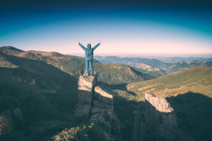 Happy hiker. Instagram stylisation. Hiker standing on a cliffs edge with raised hands and welcome the mountain valley. Instagram stylisation Stock Photo
