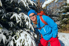 Happy hiker man in winter forest enjoying life in sunny winter d Royalty Free Stock Images