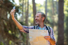 Happy hiker with map taking a selfie Royalty Free Stock Photos