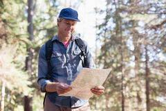 Happy hiker reading map in forest Royalty Free Stock Photos