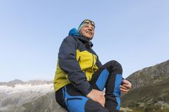 Happy hiker sits on a rock and enjoys the view Stock Photography
