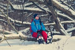 Happy hiker in a snowshoes sits on the tree Royalty Free Stock Photography