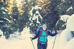 Happy hiker walks in the snow covered woods. And enjoying life. Sunny winter day. Toned image Royalty Free Stock Photography