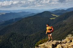 Happy hiker winning reaching life goal, success, freedom and happiness, achievement in mountains. Royalty Free Stock Photo