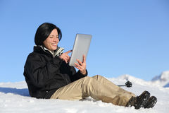 Happy hiker woman browsing a tablet on the snow Royalty Free Stock Images
