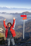 Happy hiker woman at mountain top waving hello Stock Photo