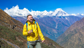 Happy Hiker in yellow Jacket drinking Tea in Mountains Stock Photo