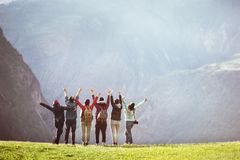 Happy hikers against mountain valley with raised arms royalty free stock image