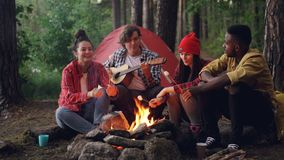Happy hikers are cooking marshmallow on fire and singing songs while handsome guy is playing the guitar during getaway