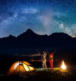 Happy hikers - guy and girl raised their hands up near bonfire and tent, enjoying incredibly beautiful starry sky Stock Photos