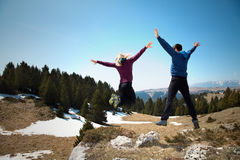 Happy hikers jumping on the top of mountain Stock Photo