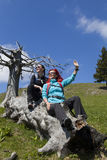 Happy hikers resting and waving hello on old tree trunk in mountain nature on sunny day Royalty Free Stock Photo
