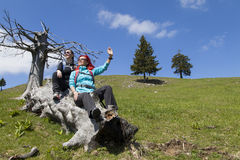 Happy hikers resting and waving hello on old tree trunk in mountain nature on sunny day Stock Photos