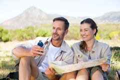Happy hiking couple reading the map on mountain trail Royalty Free Stock Photo