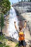 Happy hiking man cheering in success by waterfall Stock Image