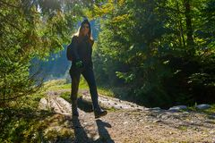 Happy hiking in the morning. Happy woman hiker with backpack on a trail in the morning Royalty Free Stock Photo