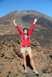 Happy hiking person celebrating. Portrait of happy hiker with arms raised in air with conquered mountain behind. Mountain volcano Pico Viejo on Teide, Tenerife stock photo